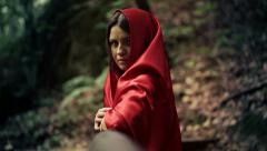 Serious beautiful mysterious woman, red riding hood in the forest HD Stock Footage