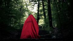 Mysterious woman, red riding hood walking in the forest HD Stock Footage