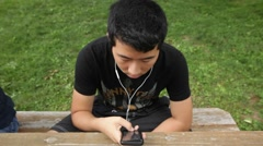 Teen Boy Listening to Music on Phone Outdoors Stock Video Stock Footage