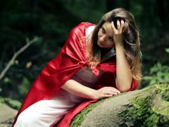 Sad beautiful woman, red riding hood sitting in the forest NTSC Stock Footage