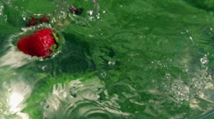 Fruits falling into water, closeup, slow motion shot Stock Footage