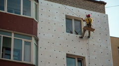 Industrial climber workers insulate the walls with Styrofoam plates - stock footage