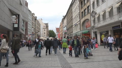 Busy shopping street tourist visit shop famous Munich city day crowd pedestrian Stock Footage