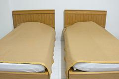 twin brown bed and blanket on white mattress at hotel - stock photo