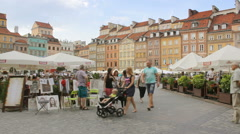 People walk in Warsaw's old town market place, panning Stock Footage