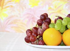 Dish with apples, grapes and oranges on abstract colored background, still li Stock Photos