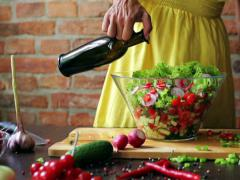 Woman adding oil from a bottle to the salad, closeup Stock Footage