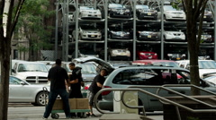 Movers in front of parking lot with stacked cars - Manhattan, New York, NYC, USA Stock Footage
