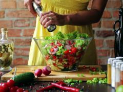 Woman adding salt to the vegetable salad, closeup Stock Footage
