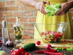 Woman adding lettuce to the vegetable salad, closeup Stock Footage