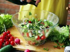 Woman adding oil to the vegetable salad, closeup Stock Footage