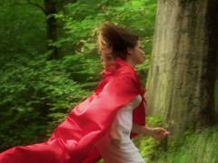 Stock Video Footage of Woman in red cape running away in forest NTSC