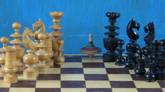 Wooden chess pieces on chessboard and whirligig humming-top Stock Footage