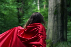 Happy woman in red cape turning round in forest, super slow motion, 240fps NTSC Stock Footage