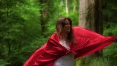 Happy woman in red cape turning round in forest HD Stock Footage
