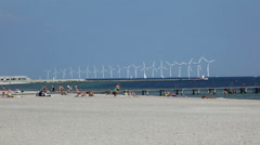 Windpower at sea, seen from a summer beach - stock footage