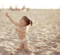 Adorable baby girl playing with soap bubbles on the beach Stock Photos