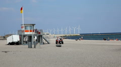 Lifeguard tower on the beach and a row of huge wind turbines at sea in the back Stock Footage