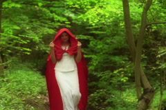 Beautiful mysterious red riding hood walking in forest NTSC Stock Footage