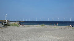Spending time on the beach on a summerday with view to huge wind turbines at sea Stock Footage