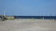 Stock Video Footage of Spending time on the beach on a summerday with view to huge wind turbines at sea