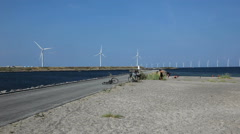 From the end of the beach you can see the huge wind turbines at sea Stock Footage