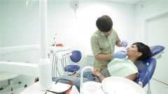 Dentist standing over the patient makes her teeth inspection - stock footage