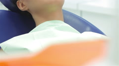 The dentist puts a pretty girl lying in the dental chair protective red glasses Stock Footage