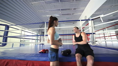 Young and successful boxing coach welcomes female athlete Stock Footage