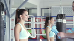 Young attractive female athlete receives from the hands of his coach dumbbells Stock Footage