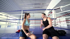 Girl athlete and fitness instructor talking and smiling to each other Stock Footage