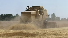 Combine harvester, straw chopper + zoom out - village Roodeschool in background Stock Footage