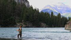 Canada Alberta Banff Bow River fisherman casting and mountain 3 Stock Footage