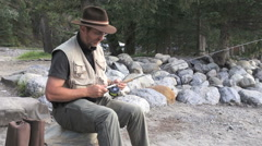 Canada Alberta Banff Bow River fisherman sits with gear 5 Stock Footage