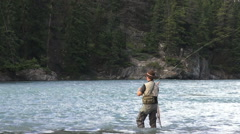 Canada Alberta Banff Bow River fisherman pays out line and casts 6 Stock Footage