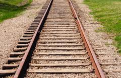 Receding train tracks near grass. Stock Photos