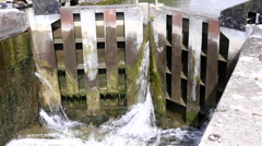 Caen Canal Locks. A view of a closed gate with water pouring through - stock footage