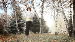 Female doing Yoga morning exercise in the autumnal park Stock Footage