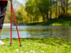 nordic walking. red sticks on grass in park - stock photo
