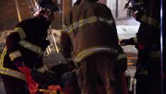 Injured fireman helped onto stretcher by colleagues Stock Footage