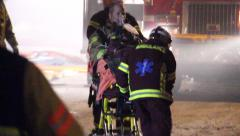Paramedics pulling away injured fireman towards bright light Stock Footage