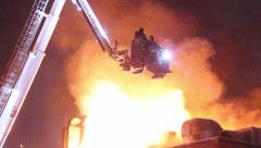 Firemen in hydraulic platform with heavy fire Stock Footage