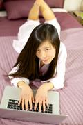 happy asian girl in bed with pc - stock photo