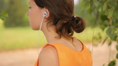 Pretty young girl looking ahead, relaxing, listening to music Stock Footage