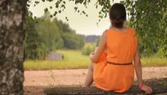 Brunette girl sits on the bench near the road and trees, listens to music Stock Footage