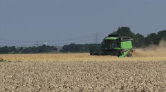 Combine harvester in northern sea clay area of The Netherlands + zoom out Stock Footage
