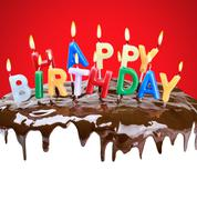 Lighted candles on his birthday on a birthday cake Stock Photos