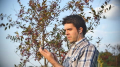 On phone mp3 player in park Stock Footage