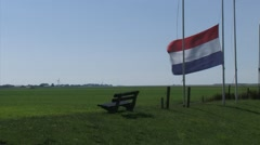 Dutch flag at half-mast in strong wind on a dike - Eemspolder, The Netherlands Stock Footage