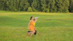 Two young kids running in the field, dreaming, a paper plane Stock Footage